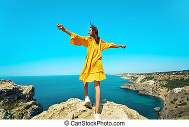 Rear view of taned traveler woman standing on top rock beach with open arms, bright yellow dress and hair blowing in the wind.