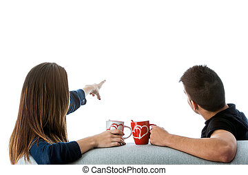 Rear view of teen couple pointing.