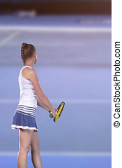 Rear view of tennis player serving during a match