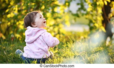 Rear view of the cute baby-girl sitting on the green grass...