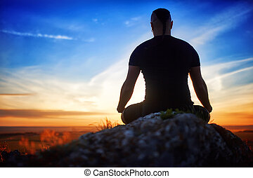 Rear view of the fit young man meditating yoga in lotus pose on the rock at beautiful sunset.