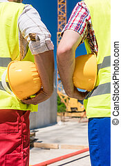 Rear view of the hands of two workers holding yellow hard hats