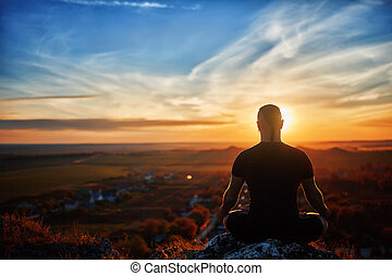 Rear view of the man meditating yoga in lotus pose on the rock at sunset.