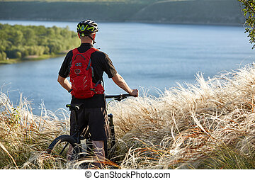Rear view of the young cyclist standing with mountain bike against beautiful river.