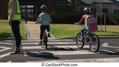 African American and Caucasian girls riding bicycles, crossing the road, carrying their schoolbags on their way to school, in slow motion. Elementary school children, road safety.