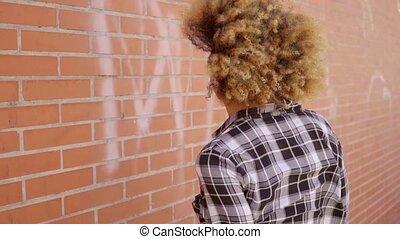 Rear View Of Walking Woman Along A Brick Wall - Rear view of...