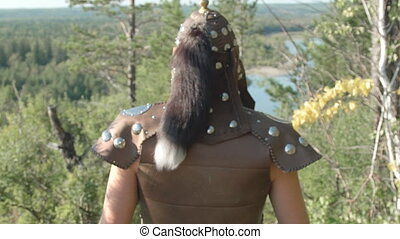 Rear view of warrior in old armor with fur that goes forest...