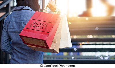 Rear view of woman holding Black Friday shopping bag while...