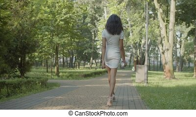 Rear view of slim attractive long-legged african american female in stylish high heel shoes and white mini dress holding clutch bag, walking along park alley gracefully on summer day.