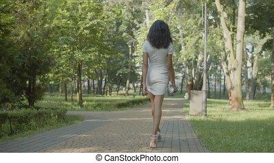 Rear view of woman in high heels walking in park - Rear view...