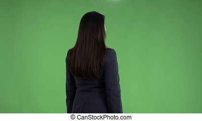 Rear view of woman meets someone looking at watch and waving her hand against green screen