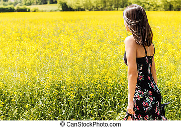 Rear view of woman next to yellow flower field.