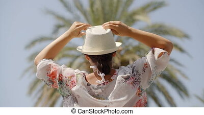 Rear View of Woman on Palm Beach with Open Arms