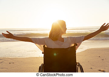 Rear view of woman on wheelchair with her arms wide open at the beach