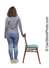 rear view of woman playing with a chair in white background