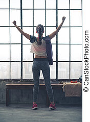 Rear view of woman rejoicing in city loft gym - YES. I did...