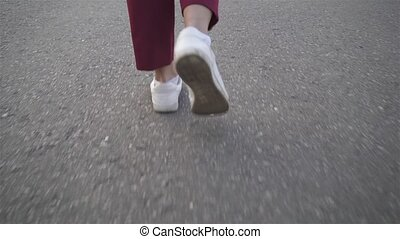 Rear view of woman s legs walking on a road