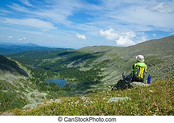 woman sitting on rock at mountain peak