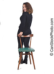 rear view of woman standing on a chair in white background, looking at camera
