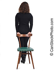 rear view of woman standing on a chair in white background