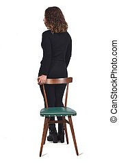 rear view of woman standing on a chair in white background, profile