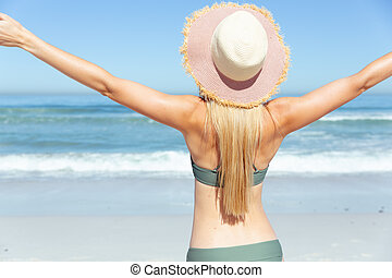 Rear view of woman standing with her arms wide open on the beach