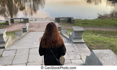 Rear view of woman walking down stone steps to Marienthal pond in Pavlovsk park