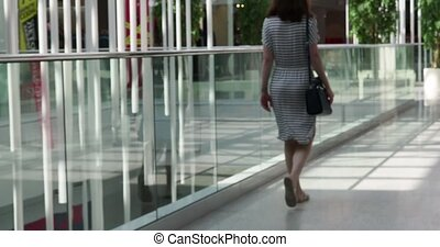 Rear view of woman walking in shopping center.