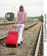 Rear view of woman walking on rail