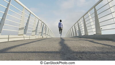 Rear view of woman wearing hijab running - Low angle rear ...