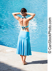 Rear view of woman with hands behind head standing at poolside