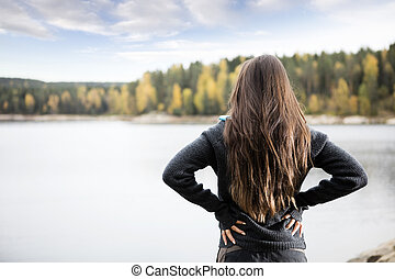 Rear View Of Woman With Hands On Hips Standing By Lake