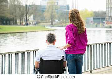 Woman With Her Disabled Husband On Wheelchair
