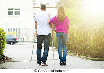 Rear View Of Woman With Her Disabled Husband