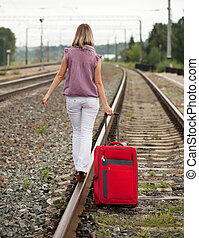 woman with luggage walking on rail