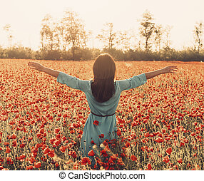 Rear view of woman with raised arms in flower meadow.