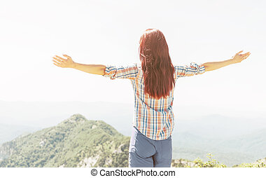 Rear view of woman with raised arms in mountains.