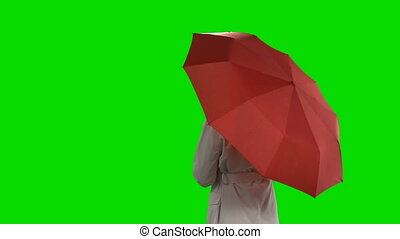 Rear view of woman with red umbrella waving her hand against green screen