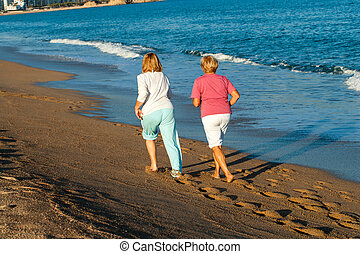 Rear view of women jogging on beach.