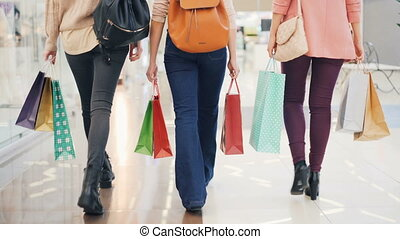 Rear view of women's legs in jeans walking in shopping mall, slender girls are carrying bright paper bags with purchases. Customers, buying things and leisure concept.
