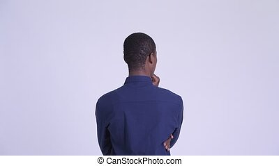 Rear view of young African businessman directing and...