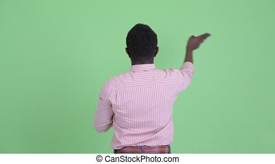 Rear view of young African businessman touching something