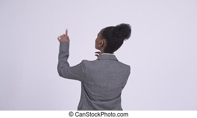 Rear view of young African businesswoman directing and...