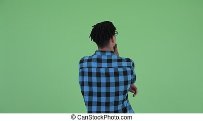 Studio shot of young handsome African hipster man with dreadlocks against chroma key with green background