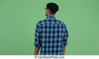 Rear view of young African hipster man touching something