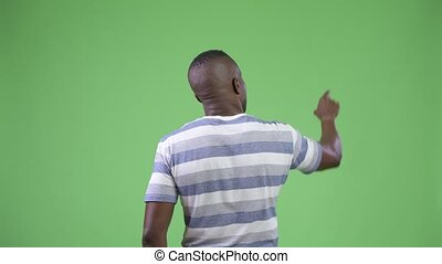 Rear view of young African man directing and pointing finger...
