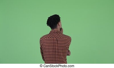 Rear view of young African man directing and pointing finger