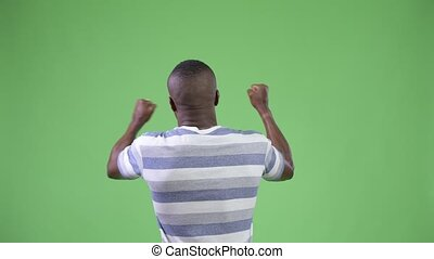 Rear view of young African man looking excited