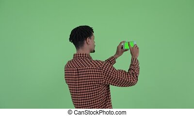 Rear view of young African man taking picture phone