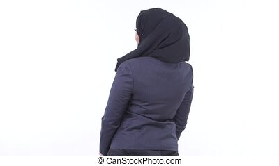 Rear view of young African Muslim businesswoman thinking and looking around